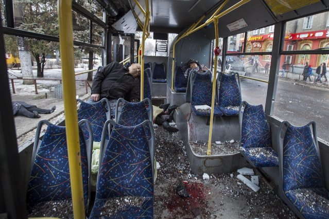 Passengers killed when a trolley bus was damaged by a mortar shell are seen in interior of the bus and outside, left, in Donetsk, eastern Ukraine, Thursday, January 22, 2015. (Photo by Igor Ivanov/AP Photo)
