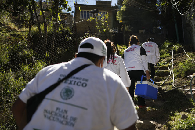 A medical team climbs uneven worn steps up a hillside to reach the home of Maria del Socorro Fuentes Chirino, 64, to administer a shot of the AstraZeneca coronavirus vaccine, in rural San Lorenzo Acopilco on the outskirts of Mexico City, Thursday, February 18, 2021. Mexico City's health department is sending teams of medical workers to give in-home vaccinations for elderly residents unable to reach vaccination centers. (Photo by Rebecca Blackwell/AP Photo)