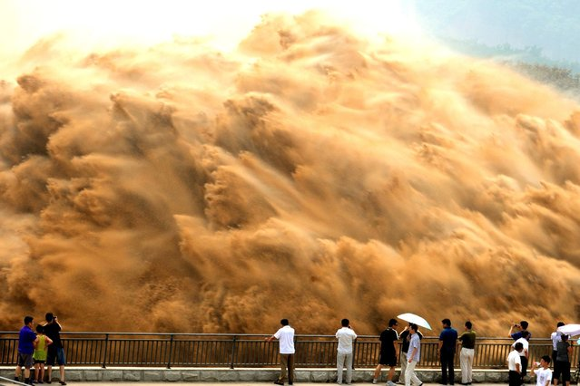 Visitors watch water gushing from the section of the Xiaolangdi Reservoir on the Yellow River, during a sand-washing operation in Jiyuan, on July 9, 2013. (Photo by China Daily)