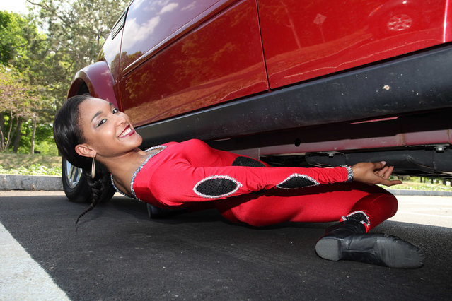 Shemika Charles limbos under her car at Niagara Falls State Park on May 28, 2015 in Buffalo, New York. A world record holding limbo queen thinks she has become the first person to shimmy under a car. Shemika Charles amazed herself and onlookers when she bent over backwards to get underneath the SUV earlier this week. The supple 22-year-old entered the record books in 2010 when she limboed down to an incredible eight and a half inches – the height of a beer bottle. (Photo by Ruaridh Connellan/Barcroft USA)