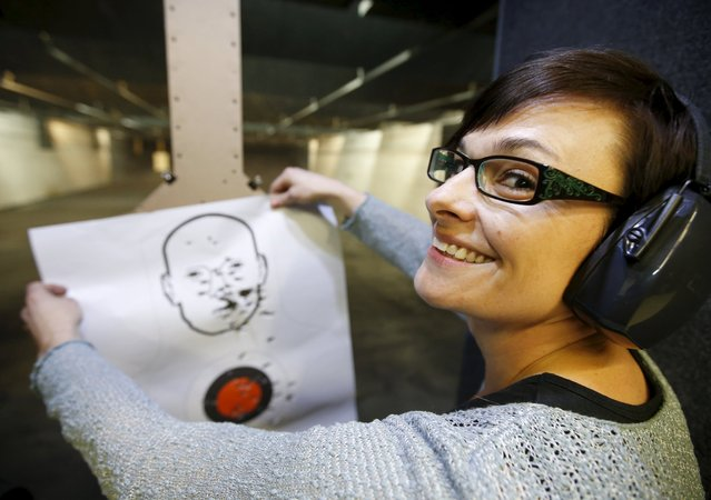 First time gun owner, Jessie Palmieri holds a target she shot with a H&K VP9 9mm gun at the Ringmasters of Utah gun range, in Springville, Utah on December 18, 2015. (Photo by George Frey/Reuters)