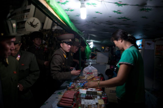 "Noth Korean soldiers buy snacks as they leave an ""Arrirang Festival mass games display"" at the 150,000-seat Rungnado May Day Stadiumin Pyongyang on July 26, 2013. Arrirang performances feature some 100,000 participants to create a 'synchronized socialist-realist spectacular in a 90 minute display of gymnastics, dance, acrobatics, and dramatic performance, in a highly politicized package' according to the China-based North Korean travel company Koryo Tours. North Korea is preparing to mark the 60th anniversary of the end of the Korean War which ran from 1950 to 1953, with a series of performances, festivals, and cultural events culminating with a large military parade. (Photo by Ed Jones/AFP Photo)"