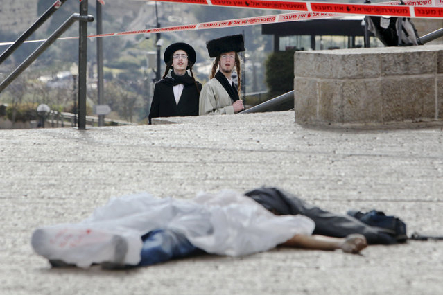 Ultra Orthodox Jews look at the body of an alleged Palestinian assailant in Jerusalem Saturday, December 26, 2015. According to a police spokeswoman, policemen approached a man who drew their suspicions just outside the Old City for following a pair of Jewish worshippers. Then he pulled out a knife and tried to stab one of them, officers opened fire and killed the assailant. (Photo by Mahmoud Illean/AP Photo)