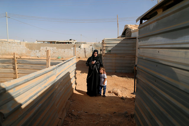 Fadwe Arashed, 25, the Syrian widow of a rebel fighter poses for a photograph with her children, as they hold a photograph of her late husband in Zaatari camp in Jordan October 14, 2016. Arashed's husband was killed during fighting againt forces loyal to Syria's President Bashar al-Assad near Daraa. (Photo by Ammar Awad/Reuters)