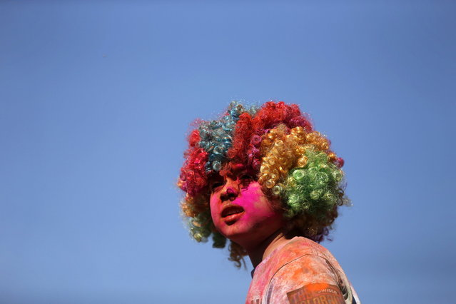A child wearing a wig looks at the stage after finishing the Colour Run at Centennial Park in Sydney August 25, 2013. According to organizers, 15,000 runners registered to complete the 5km (3 miles) course in Centennial Park on Sunday, being covered in blue, pink, orange and yellow powder on their way to finish line. (Photo by Daniel Munoz/Reuters)