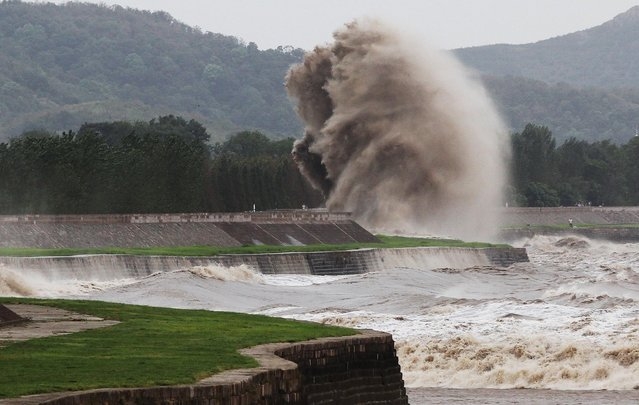 A tidal wave hits a bank along the Qiantang River on August 22, 2013 in Haining, China. The 12th typhoon Trami landed in Fujian province at 2:40 am and led gales and heavy rainfalls in east China. (Photo by ChinaFotoPress)