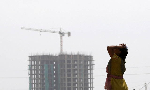 A labourer takes a break from her work at the construction site of a residential complex in Noida on the outskirts of New Delhi, India, August 20, 2015. (Photo by Adnan Abidi/Reuters)
