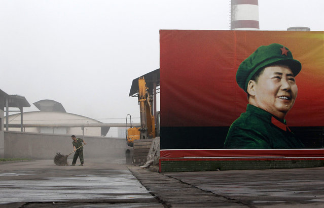A worker cleans near a poster of the late Chairman Mao Zedong at a thermal power plant of the Nanjie Cun Group in Nanjie village of Luohe city in China's central Henan province September 25, 2012. Nanjie village, with more than 3,100 residents, is touted to be one of the remaining models of communist China, where the principles of morality and collectivism of the late Chairman Mao still strictly guide the people's daily lives. (Photo by Jason Lee/Reuters)
