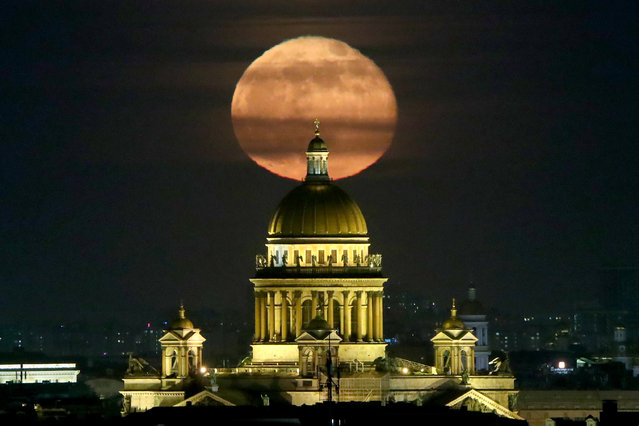 The moon is seen in the sky over St Isaac's Cathedral in St Petersburg, Russia on March 29, 2021. (Photo by Peter Kovalev/TASS)