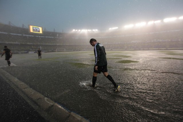 A FIFA referee checks the field during a downpour before the start of the 2014 World Cup qualifying soccer match between Colombia and Ecuador in Barranquilla, on September 7, 2013. (Photo by John Vizcaino/Reuters)