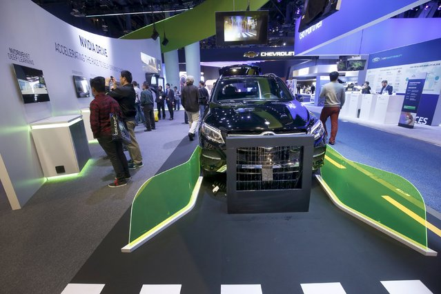 Attendees look over displays on autonomous driving at the Nvidia booth during the 2016 CES trade show in Las Vegas, Nevada January 8, 2016. (Photo by Steve Marcus/Reuters)
