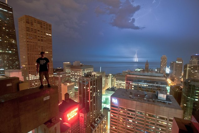 Bradley Garrett stands on the edge of the Ritz-Carlton Chicago as lightning strikes in the distance in Chicago, US. (Photo by Bradley L. Garrett/Barcroft Media)