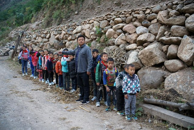 "Students from ""the cliff village"" in Atule'er line up before climbing newly-constructed steel ladders after school to go home for holidays, in Liangshan Sichuan province, China, November 19, 2016. (Photo by Reuters/Stringer)"