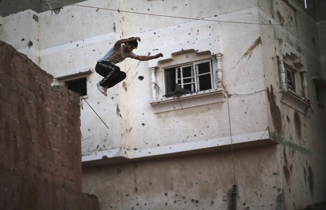 A Palestinian youth jumps from a house, which witnesses said was damaged during a seven-week Israeli offensive, as he practices his Parkour skills in the Shejaia neighborhood east of Gaza City, October 1, 2014. (Photo by Mohammed Salem/Reuters)
