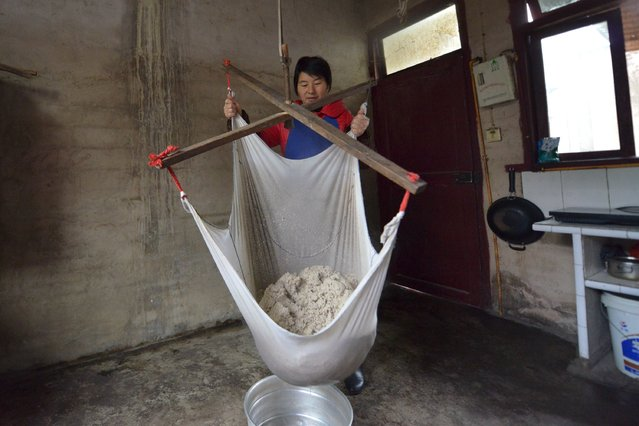 """A woman uses a filter cloth to filter out impurities while making traditional candy """"Matang"""", in preparation for the upcoming Chinese Lunar New Year in Yuqing County, Zunyi, Guizhou Province, China, January 18, 2016. (Photo by Reuters/China Daily)"""