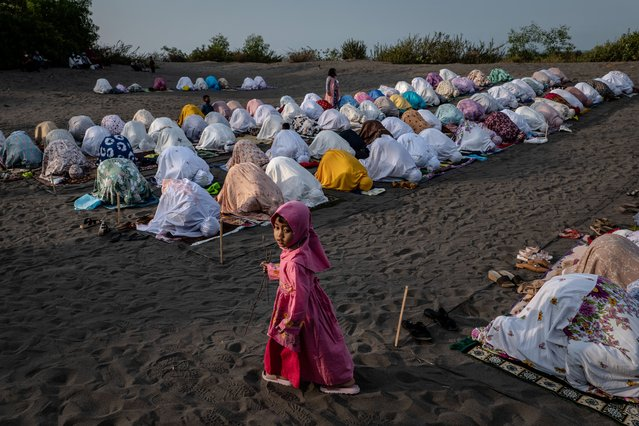 """Indonesian muslims perform an Eid Al-Fitr prayer on the """"sea of sands"""" at Grogol village on May 13, 2021 in Yogyakarta, Indonesia. Eid al-Fitr marks the end of Ramadan, during which Muslims in countries around the world spend time with family, offer gifts and often give to charity. The Indonesian government has banned domestic travel to prevent the spread of COVID-19, preventing people from returning home for festivities. (Photo by Ulet Ifansasti/Getty Images)"""