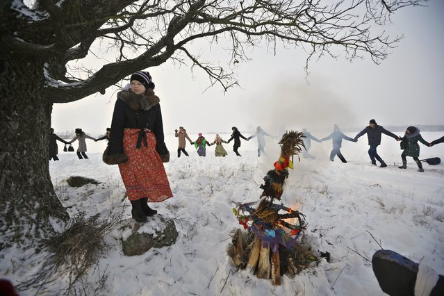 Belarusians celebrate a Pull the Kolyada Up the Oak rite in the village of Martsiyanauka, some 77 km (48 miles) east of capital Minsk, Belarus, Thursday, January 21, 2016. The merry ancient rite Pull the Kolyada Up the Oak marks the end of Orthodox Christmas celebrations in Belarus. On Jan. 21 a wheel, the so-called Kolyada, would be pulled up an oak or any old tree. The Belarusians believed that the ritual heralds a good harvest, luck and happiness for the entire  year. (Photo by Sergei Grits/AP Photo)