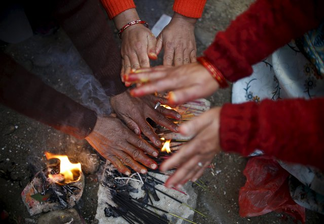 Hands of devotees try to keep them warm near burning incense during the Swasthani Brata Katha festival at Sankhu in Kathmandu, Nepal, January 24, 2016. (Photo by Navesh Chitrakar/Reuters)
