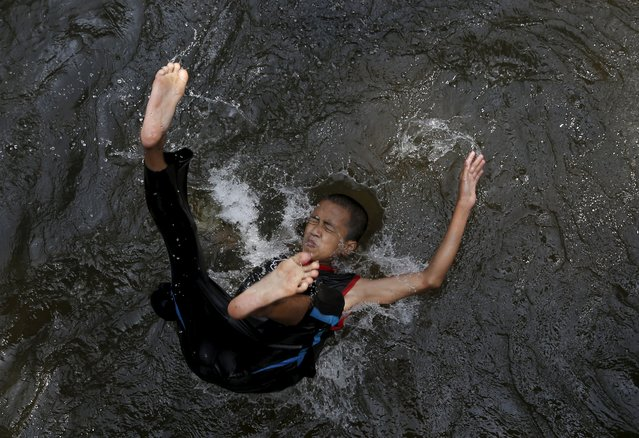 A boy plays in the river during a week-long break from school, outside Kuala Lumpur, March 19, 2015. (Photo by Olivia Harris/Reuters)