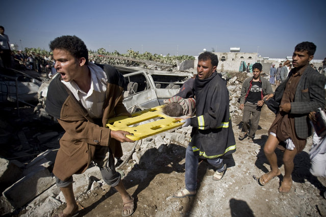 People carry the body of a child they uncovered from under the rubble of houses destroyed by Saudi airstrikes near Sanaa Airport, Yemen, Thursday, March 26, 2015. Saudi Arabia launched airstrikes Thursday targeting military installations in Yemen held by Shiite rebels who were taking over a key port city in the country's south and had driven the embattled president to flee by sea, security officials said. (Photo by Hani Mohammed/AP Photo)