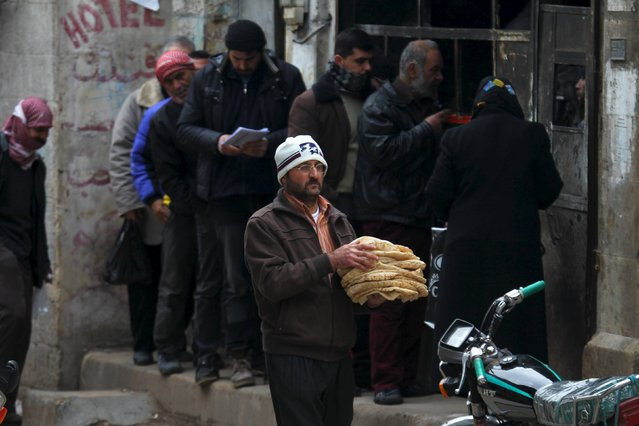 A man carries bread as he walks past people queuing in Idlib city, Syria January 23, 2016. (Photo by Ammar Abdullah/Reuters)