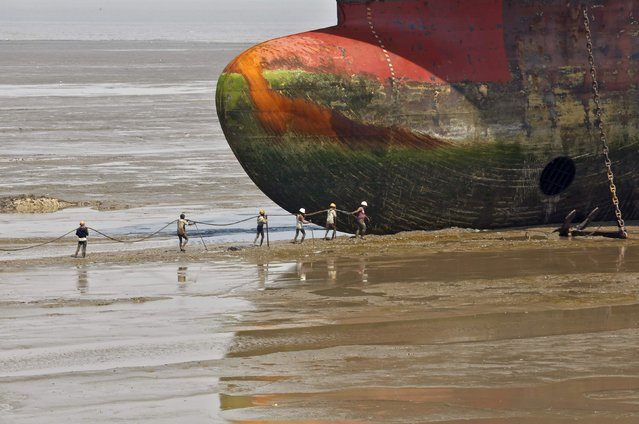 Workers carry a rope line to fasten a decommissioned ship at the Alang shipyard in the western Indian state of Gujarat, March 27, 2015. The European Union plans to impose strict new rules on how companies scrap old tankers and cruise liners, run aground and dismantled on beaches in South Asia. (Photo by Amit Dave/Reuters)