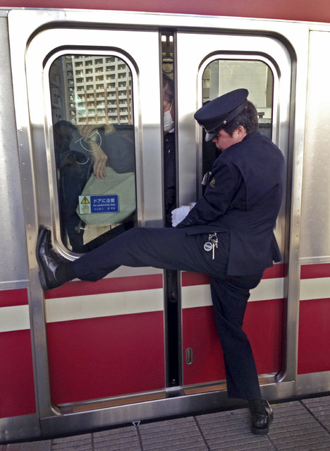 A station attendant stretches out to open a door for a passenger to get in a train car at a station in Kawasaki, near Tokyo, during a morning rush hour, Monday, March 30, 2015. (Photo by Shuji Kajiyama/AP Photo)