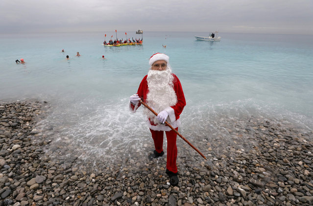 A man dressed as Santa Claus stands on the shore during the traditional Christmas season swim in Nice, France, December 16, 2018. (Photo by Eric Gaillard/Reuters)
