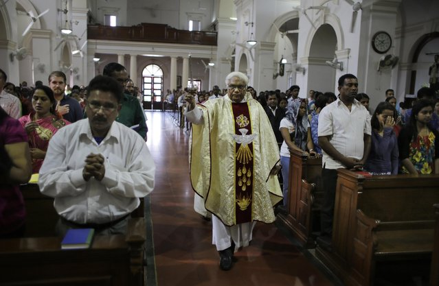 An Indian Catholic priest sprinkles holy water on believers at the Sacred Heart Cathedral on the occasion of Easter Sunday, in New Delhi, India, Sunday, April 5, 2015. (Photo by Altaf Qadri/AP Photo)
