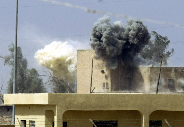 A building receives tank fire from U.S. Marine Expeditionary Unit tanks beside the port of Umm-Qasr in southern Iraq as pockets of Republican Guard resistance remain in a residential area beside the port, March 2003. (Photo by Desmond Boylan/Reuters)