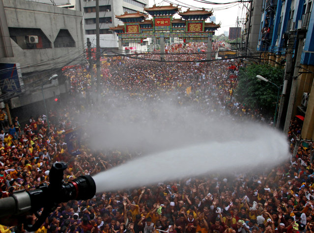 A volunteer with the fire service douses devotees with water as they take part in the annual procession of the Black Nazarene in Manila, Philippines, January 9, 2017. (Photo by Czar Dancel/Reuters)