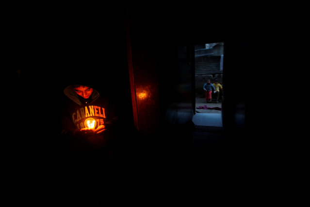 A Palestinian boy holds candles to light his family's house during a power cut in Beit Lahiya in the northern Gaza Strip January 11, 2017. (Photo by Mohammed Salem/Reuters)