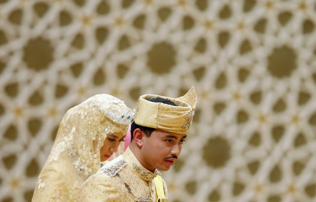 "Brunei's newly wed royal couple, Prince Abdul Malik and Dayangku Raabi'atul 'Adawiyyah Pengiran Haji Bolkiah, leave the ""bersanding"" or enthronement ceremony at their wedding in the Nurul Iman Palace in Bandar Seri Begawan April 12, 2015. (Photo by Olivia Harris/Reuters)"