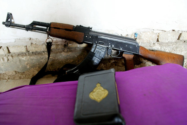 An AK-47 rifle and a Quraan are pictured against a wall in a fighters nest on November 7, 2004 in the city of Fallujah, Iraq. (Photo by Ghaith Abdul-Ahad/Getty Images)