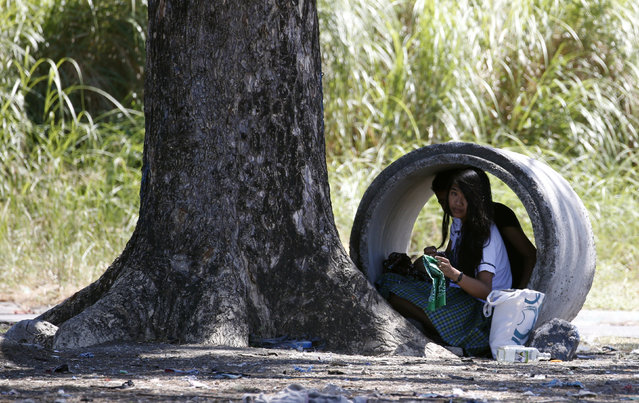 Students sit inside a drainage culvert used for flood control in Las Pinas, Metro Manila February 22, 2016. (Photo by Erik De Castro/Reuters)