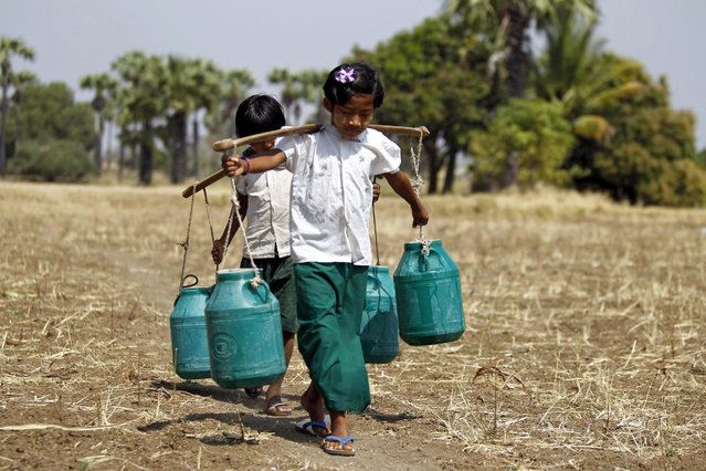 Children carry buckets to collect drinking water at Sapa village, in the outskirts of Mandalay, Myanmar, 23 February 2016. Weather experts say Myanmar's norther state Mandadaly might suffer from drought due to the El Nino weather phenomenon. The summer 2016 is expected to see the worst drought situation and the shortage of drinking water will also be a problem in the villages. (Photo by Hein Htet/EPA)