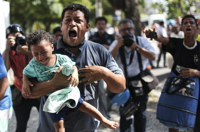 A man runs carrying his daughter during a forced eviction by police from a building that belongs to the soccer club Flamengo, in Rio de Janeiro, Brazil, April 14, 2015. Weeks ago a group of homeless people occupied the building. After their eviction, they expect now a housing solution by government. (Photo by Antonio Lacerda/EPA)