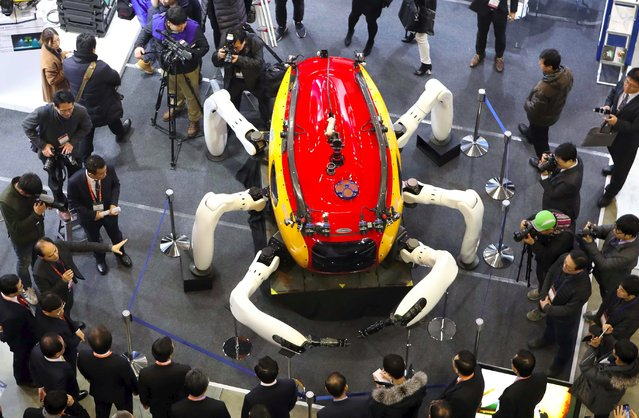Visitors look at an undersea exploration robot during a drone show at the BEXCO Exhibition Hall in the southeastern port city of Busan on January 19, 2017. The exhibition is underway in Busan for a three-day run showcasing a variety of drones ranging from light unmanned aerial vehicles to toy drones. (Photo by AFP Photo/Stringer)