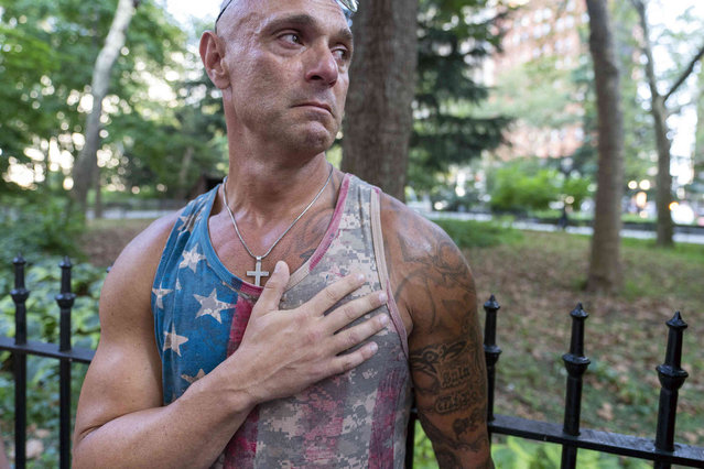 Angelo Boncaraglio, of Staten Island, holds his hand to his heart during the national anthem during a demonstration against COVID-19 vaccination mandates, Wednesday, August 25, 2021, in New York. (Photo by Mary Altaffer/AP Photo)