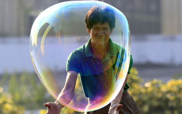 A man plays with a bubble while celebrating New Year's day at a park in Manila January 1, 2014. (Photo by Romeo Ranoco/Reuters)