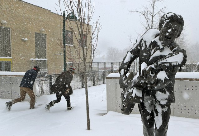 Two people duck into the blowing snow as they leave the U City Loop next to the statue of Chuck Berry on Sunday morning, January 5, 201, in St. Louis. Heavy snow combined with strong winds and bitter cold created a dangerous winter mix Sunday over much of Missouri. (Photo by J. B. Forbes/AP Photo/St. Louis Post-Dispatch)