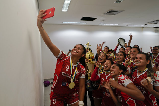 Salcomp soccer players take a selfie in the dressing room after winning the Peladao amateur soccer tournament at Arena da Amazonia in Manaus, Brazil, Saturday, February 16, 2019. The majority of Peladao players do not dream of turning professional, although a few have managed to do that with small clubs in Brazil's northern states. (Photo by Victor R. Caivano/AP Photo)