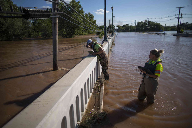 United States Geological Survey workers measure the floodwaters along the Raritan River in Somerville, N.J. Thursday, September 2, 2021. A stunned U.S. East Coast faced a rising death toll, surging rivers, tornado damage and continuing calls for rescue Thursday after the remnants of Hurricane Ida walloped the region with record-breaking rain. (Photo by Eduardo Munoz Alvarez/AP Photo)