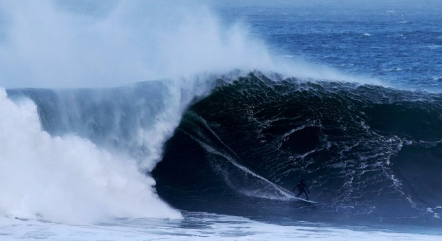 A surfer rides a wave at Mullaghmore, Co. Sligo, on January 6, 2014. (Photo by Brian Lawless/PA Wire)