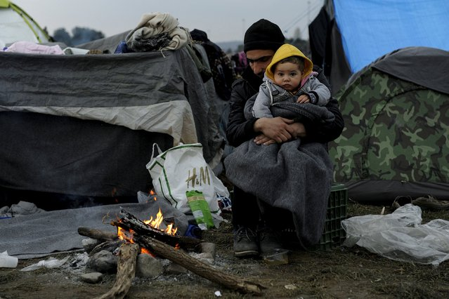 A refugee holding a baby warms himself next to a bonfire at a makeshift camp set up by stranded refugees and migrants who are waiting to cross the Greek-Macedonian border, near the Greek village of Idomeni, February 29, 2016. (Photo by Alexandros Avramidis/Reuters)
