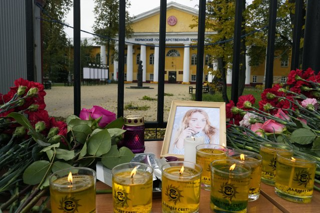 Flowers, candles and a portrait of one of victims are displayed on a table outside the Perm State University in Perm, about 1,100 kilometers (700 miles) east of Moscow, Russia, Tuesday, September 21, 2021. (Photo by Dmitri Lovetsky/AP Photo)