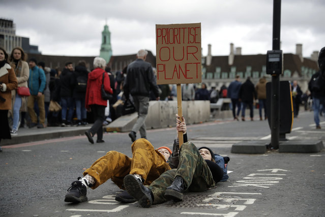 Youngsters lay down as they take part in a student climate protest at the bottom of Westminster Bridge in London, Friday, March 15, 2019. Students in more than 80 countries and territories worldwide plan to skip class Friday in protest over their governments' failure to act against global warming. The coordinated 'school strike' was inspired by 16-year-old activist Greta Thunberg, who began holding solitary demonstrations outside the Swedish parliament last year. (Photo by Matt Dunham/AP Photo)