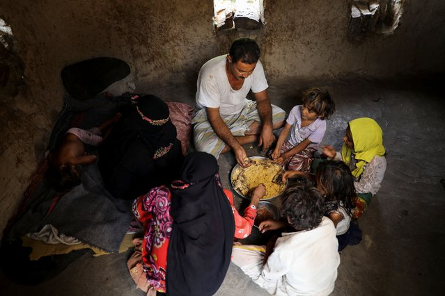 Ali al-Emadi, who works as a lumberjack, eats lunch with his family at their house in a village in Khamis Banisaad district of al-Mahweet province, Yemen, June 24, 2021. (Photo by Khaled Abdullah/Reuters)