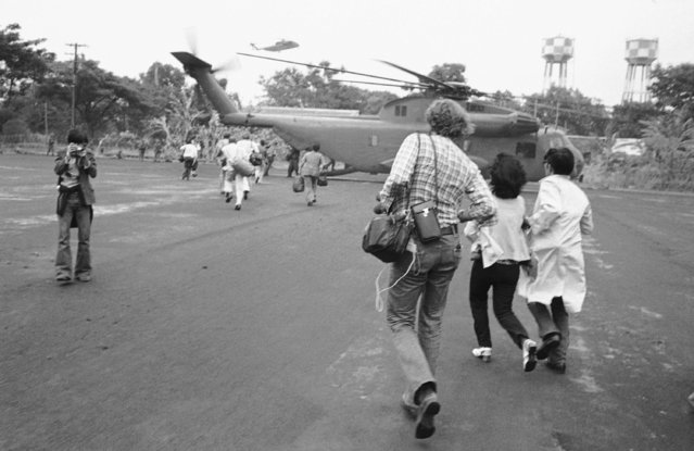 Americans and Vietnamese run for a U.S. Marine helicopter in Saigon during the evacuation of the city, April 29, 1975. (Photo by AP Photo)