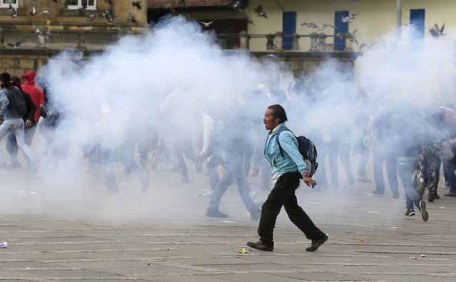 A man walks past smoke left by tear gas during clashes against police on Labor Day in Bogota, Colombia May 1, 2015. (Photo by Jose Miguel Gomez/Reuters)